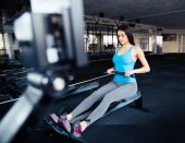 Woman doing exercise on simulator at gym — Stock Photo