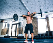 Muscular man lifting barbell — Stock Photo