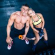 Muscular man and woman resting on bench at gym — Stock Photo #70715193