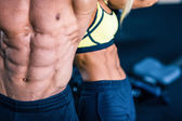 Muscular man's and strong woman's torso — Stock Photo