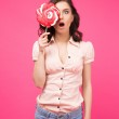 Woman covering her eye with lollipop — Stock Photo #70790151