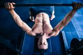 Muscular man workout with barbell on bench — Stock Photo