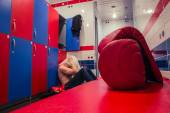 Tired man sitting on the floor in the locker room — Stock Photo