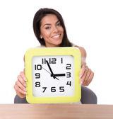 Happy businesswoman showing big clock — Stock Photo