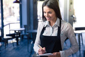 Smiling beautiful female waiter in apron — Stock Photo