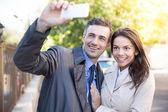 Cheerful couple making selfie photo outdoors — Stock Photo