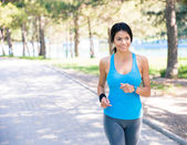 Smiling woman running in park — Stock Photo