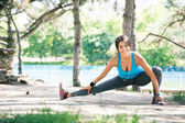 Fitness woman doing stretching exercise in park — Stock Photo