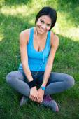 Happy fitness woman sitting on the green grass — Stock Photo