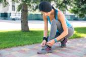 Woman tying her shoelace outdoors — Stock Photo
