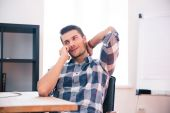 Young businessman speaking on the phone in office — Stock Photo