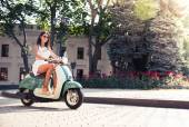 Cheerful young woman driving scooter — Stock Photo