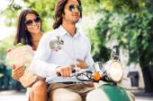 Couple driving scooter while woman holding bag full of groceries — Foto Stock