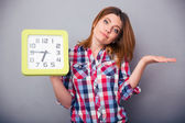 Young casual woman holding clock — Stock Photo