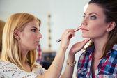 Visagist woman applying makeup — Stock Photo
