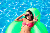 Girl showing victory sign in swimming pool — Stock Photo