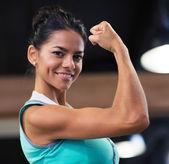 Женщина, показывая ее бицепс в тренажерный зал — Стоковое фото