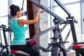 Back view portrait of a woman workout on exercises machine — Stock Photo