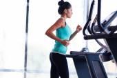 Woman running on treadmill — Stock Photo