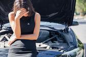 Woman standing near broken car — Stock Photo