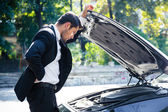 Man standing near broken car — Stock Photo