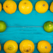Fresh organic lemons and limes on wooden background — Stock Photo #54197557