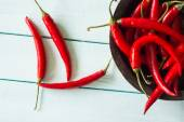 Vibrant red fresh chilli on white wood table — Stock Photo