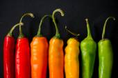 Vibrant colors on peppers on black slate bacground — Stock Photo