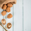 Walnuts in sack and nut cracker on table — Stock Photo #58165375
