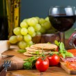 Oat crackers and parma cheese with red wine on table — Stock Photo #60777441