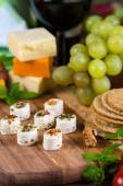 Selection of party cheese snacks with herbs on board — Stock Photo