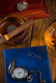 Wealthy man desk with cigars, vintage watch cognac and year plan — Stock Photo