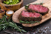 Top view on raw steak with herbs and pepper — Stock Photo