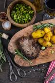 Beef steak with roasted potatoes and herbs, top view — Stock Photo