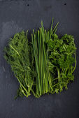 Spring garden fresh chives,parsley and dill on black slate  back — Stock Photo