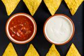 Mexican street food nachos  with salsa and cream dip on black ba — Stock Photo