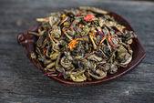 Aromatic antioxidant green tea on wooden board — Stock Photo