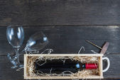 Wine in wooden case with straw and glass from above — Stock Photo