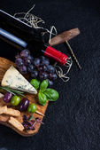Food background,rustic board with cheese herbs and wine — Stock Photo