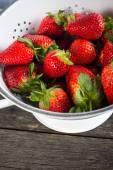 Sweet ripe strawberries in rustic colander  — Stock Photo