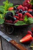 Svěží letní jahody s mátou v rustikální mísa — Stock fotografie