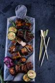 Grilled pork belly slices on marble board and veggies from above — Stock Photo
