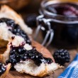 Постер, плакат: Spreading croissant with blackberry jam