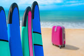 Color surf boards in a stack by ocean — Stock Photo