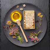 Honey, honeycomb and dried herbs on dark background — Stock Photo