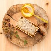 Honey, honey comb and dried herbs on wooden board — Stock Photo
