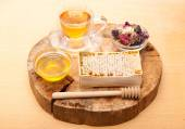 Honey comb, herbal tea and dried herbs on wooden board — Stock Photo