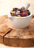 Dried herbs and flowers in mortar on wooden board — Stock Photo