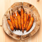 Baked carrots on wooden board in rustic style — Stock Photo