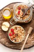 Granola with nuts, dried fruit and honey on wooden background — Stock Photo